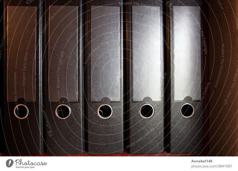 four black ring binders on a bookshelf for office or administration, business concept background folder order organization paper file data white information