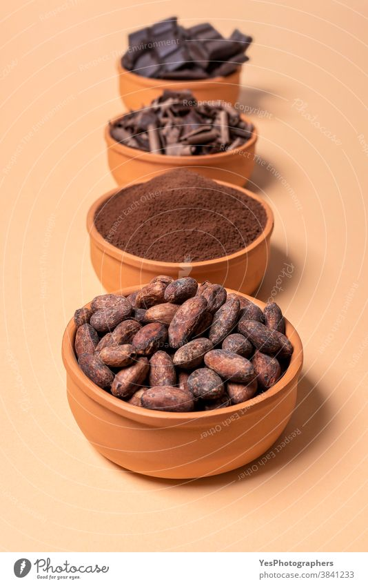Cacao beans in a bowl and chocolate isolated on beige background assortment baking bitter bowls cacao cacao beans chocolate chips chocolate chunks