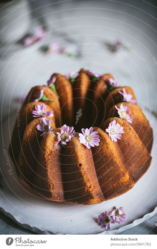 Appetizing Bundt cake with flowers on table bundt cake tasty decoration serve dessert sweet delicious kitchen plate fresh gourmet yummy baked cuisine pastry