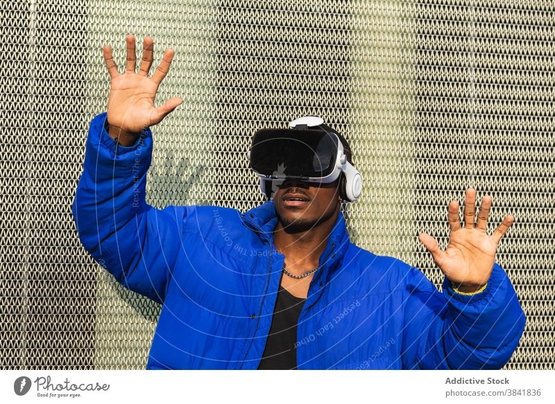 Black man experiencing virtual reality in city goggles vr glasses experience interact touch futuristic male ethnic black african american street metal fence