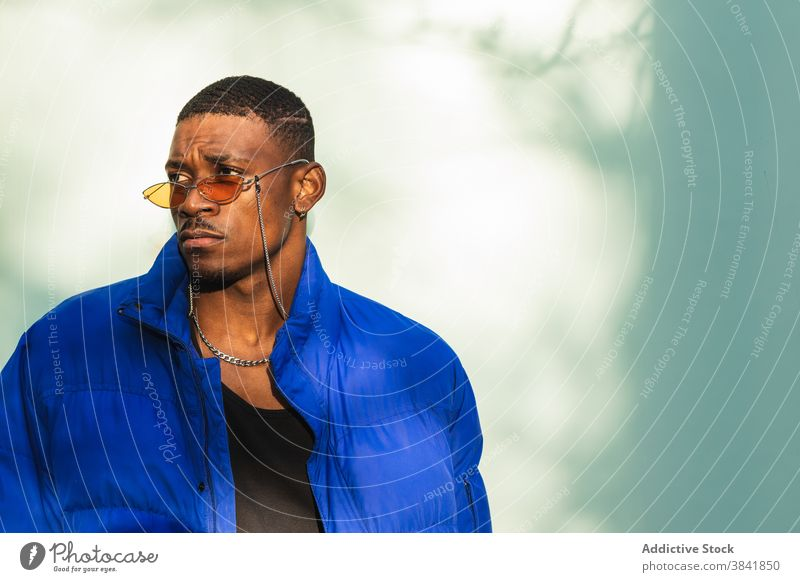 Stylish black man in sunglasses on street style orange trendy outfit determine cool urban male ethnic african american confident modern warm jacket building