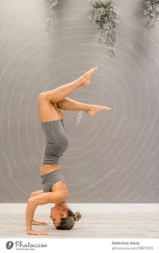 Slim woman doing yoga in Tripod Headstand pose headstand balance tripod headstand pose flexible serene asana salamba sirsasana female mindfulness practice
