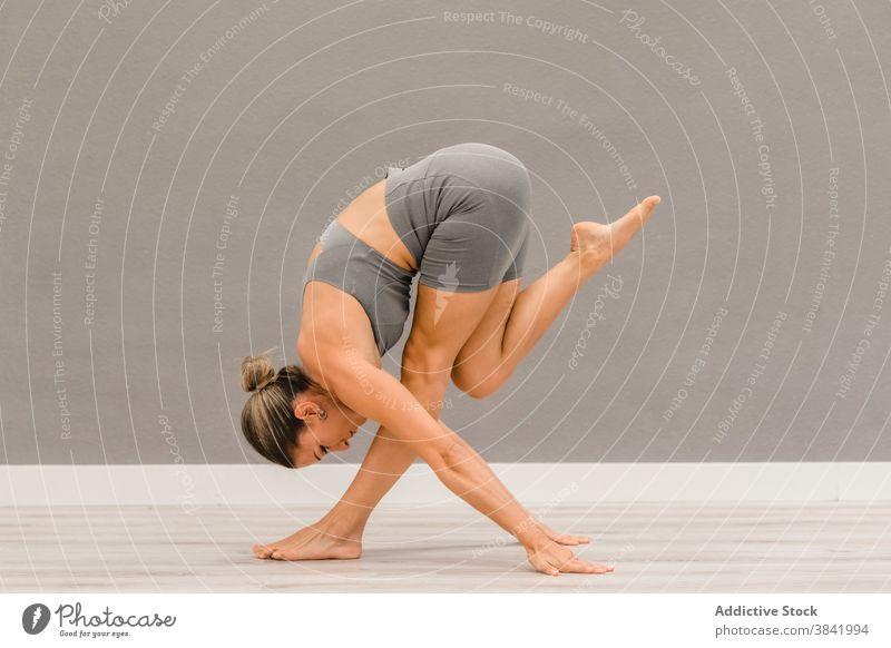 Flexible woman practicing yoga in Forward Bend pose forward bend balance flexible asana barefoot harmony calm female bright studio fit stretch wellbeing body