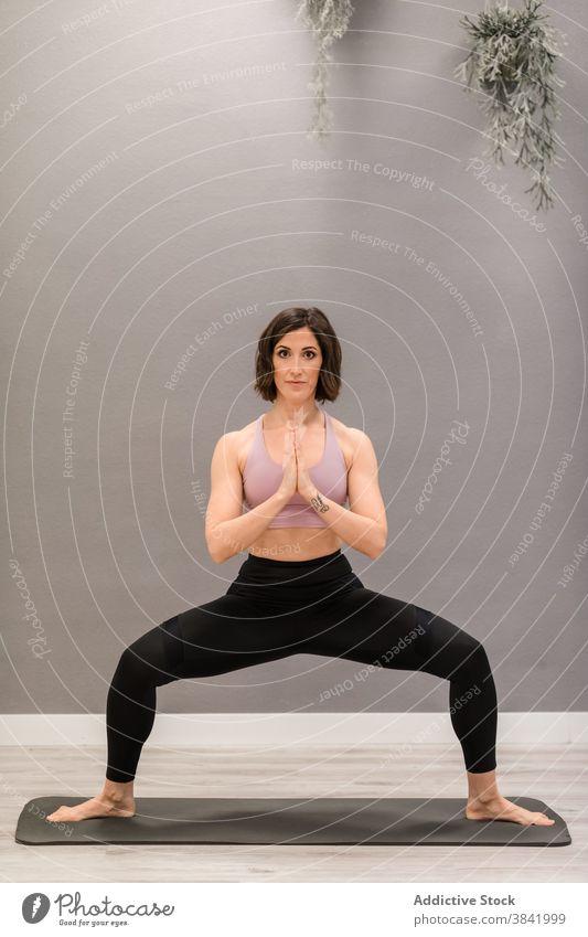 Woman in Goddess pose doing yoga at home woman goddess pose utkata konasana flexible mat recreation stress relief mindfulness female healthy practice wellness