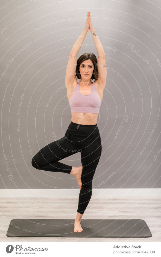 Slim woman in Tree pose on yoga mat vrksasana tree pose balance barefoot soul mindfulness stress relief female activewear content slender slim harmony home