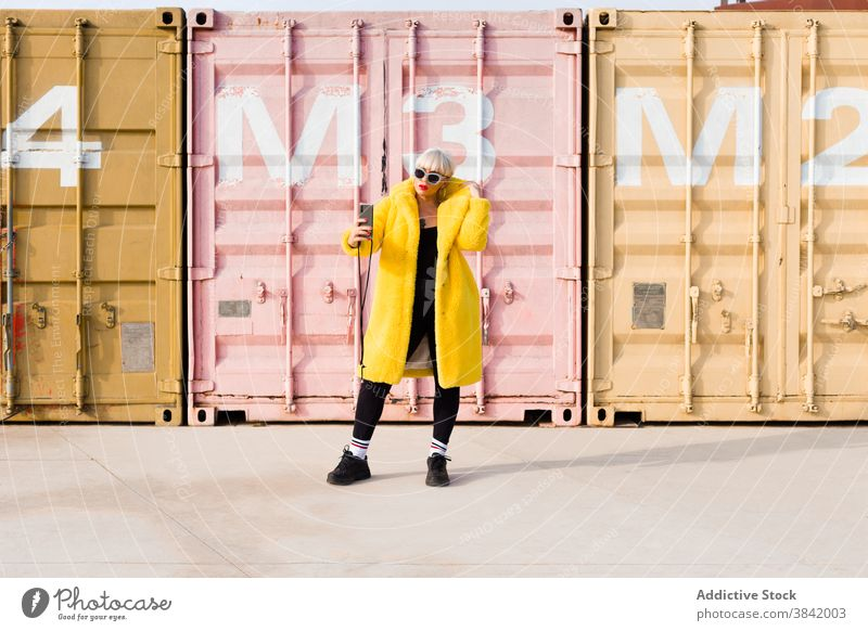 Woman in trendy wear taking selfie in city millennial outfit woman smartphone self portrait urban bright yellow female color coat street young gadget device