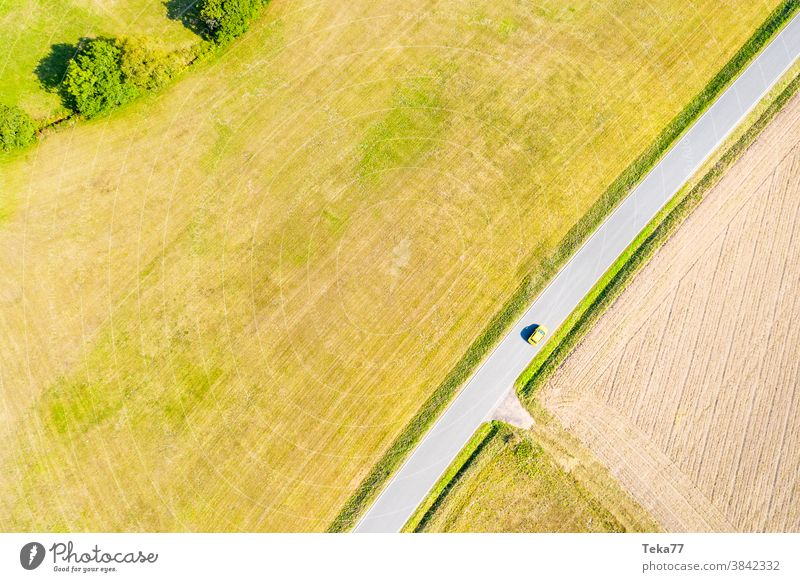 a yellow car on a country road in the summer from above td top down traffic countrsyside lone car from above concrete meadow
