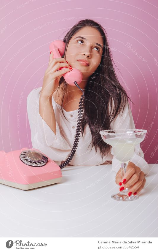 Cheerful and smiling young brunette woman with drink, uses a vintage phone. Portrait on a pink background beautiful brazilian disposable elegance fashion girl