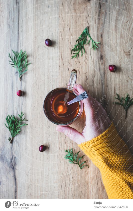 Female hand holding a glass of tea on an autumnal background. Yellow woolen sweater, partial section. Tea drinking glass Hand Woman stop hygge tea break Autumn
