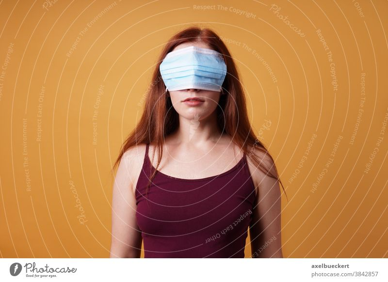 young woman wearing medical face mask over her eyes - corona denier cover covid coronavirus denial deny blind wrong protest covid-19 people adult person