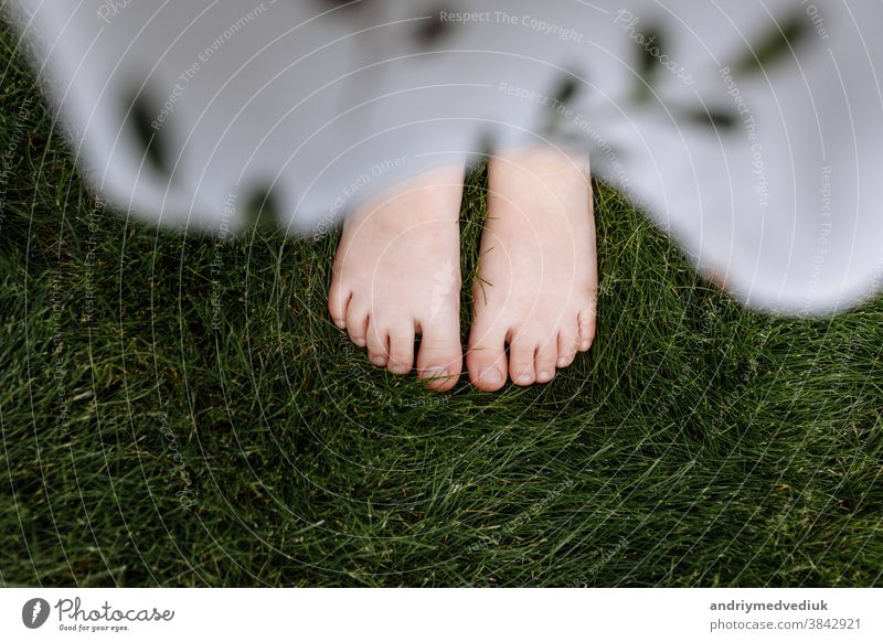 top view close up of child's bare feet on the green grass, concept of nature summer childhood girl foot baby little happy beautiful spring fun people park