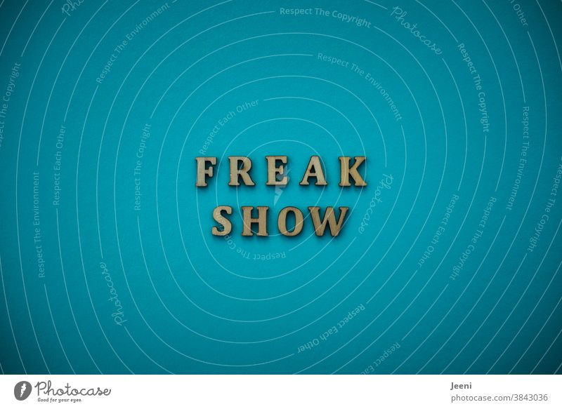 FREAKSHOW | Text on a plain background in turquoise-blue Freak show wackier Madman Human being bizarre Crazy Alarming unusual flipped out freak funny bird