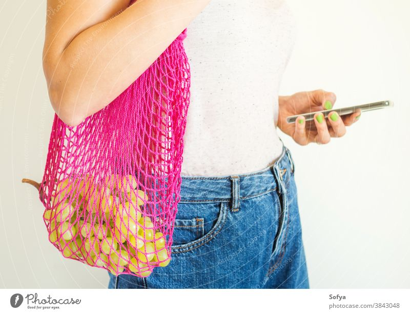Young woman with reusable mesh bag and smartphone food using mobile phone online delivery grocery fruit grapes autumn plastic sustainable digital zero waste