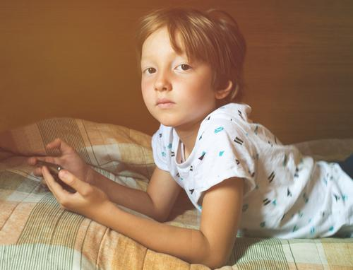 Little blonde boy playing games at smartphone child alone kid mobile using app gadget digital watching screen device school fun home indoor hands lifestyle