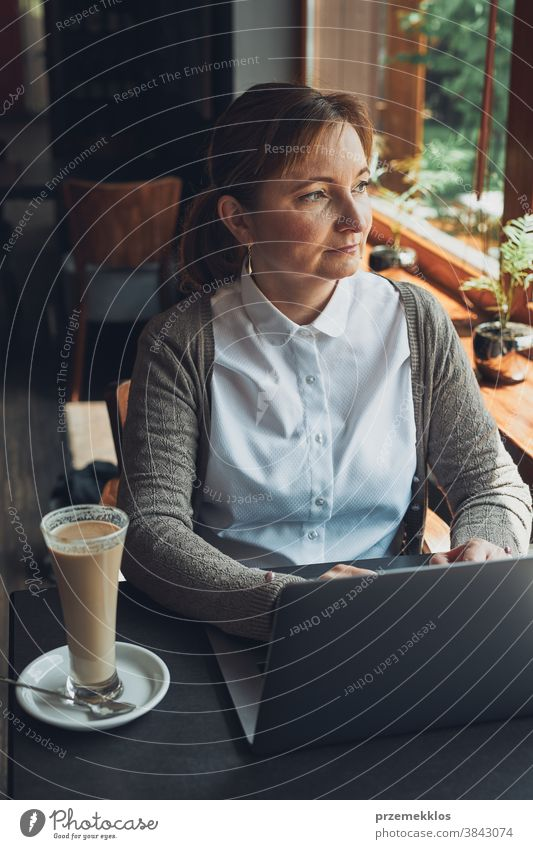 Businesswoman working remotely on her laptop managing her work sitting in a cafe business caucasian computer connection desk entrepreneur female indoors