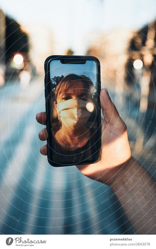 Young man having video call talking while walking downtown wearing the face mask to avoid virus infection care caucasian chat contagious corona coronavirus