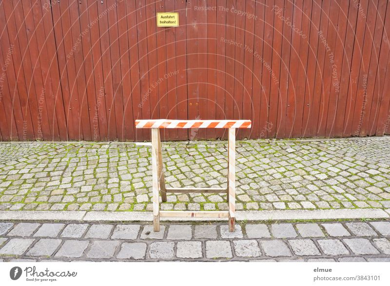 """A wooden work trestle stands partly on the road and partly on the footpath in front of a dense, red-brown wooden fence with a yellow sign """"Keep the exit free!"""