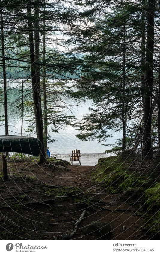 Adirondack Chair by lake with canoe in foreground adirondack chair relaxing Adventure Canoe trip Summer Vacation & Travel Lake Nature Water Day