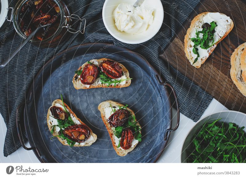 italian traditional bruschetta - bread toast with sun dried tomatoes, cream cheese, olive oil and arugula. sandwich food snack vegetable healthy herb appetizer