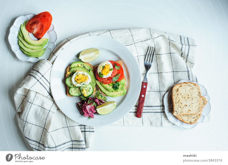 healthy vegetarian breakfast, avocado toast with cucumber, eggs, tomato and greean salad on wholegrain bread meal food lunch green sandwich diet fresh snack