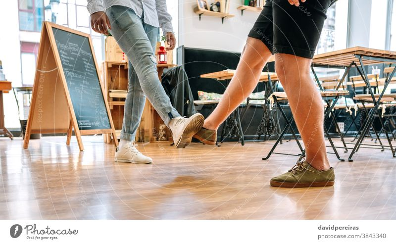 Two unrecognizable friends saluting with feet leg bump coronavirus foot greeting social distancing covid-19 unsafe avoid health pandemic protect legs quarantine