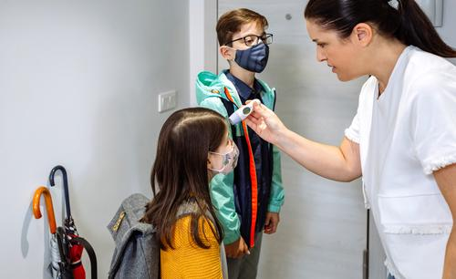 Mother checking her daughter's temperature before going to school mother thermometer fever coronavirus before going school protective mask home family indoors
