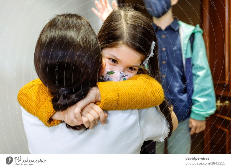 Mother hugging daughter with mask coming back from school mother after protective mask covid-19 before coronavirus son girl safety young kid child say goodbye