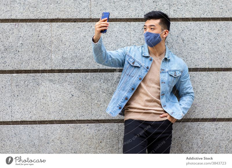 Ethnic man in mask taking selfie in city smartphone coronavirus covid 19 self portrait pandemic street male ethnic asian building medical protect device