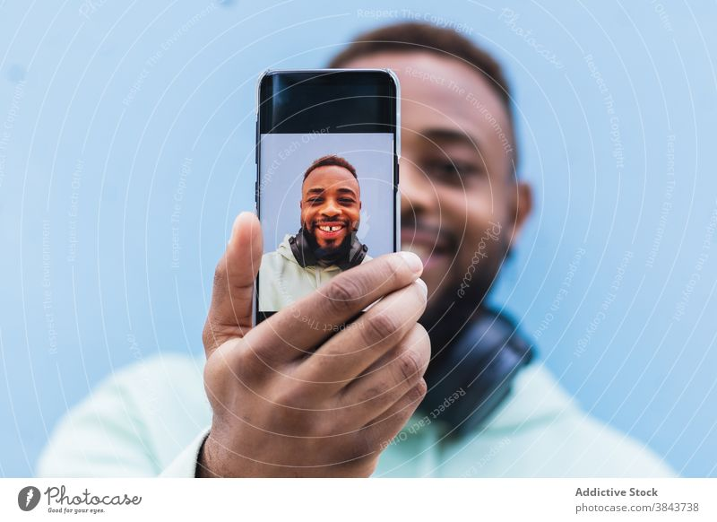 Happy ethnic man taking selfie on smartphone happy hipster cheerful mobile photography using take photo adult black african american male casual device gadget