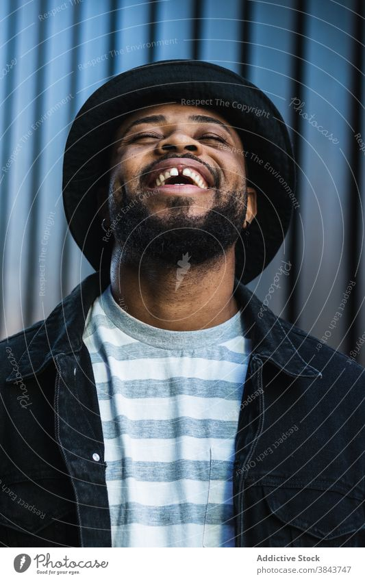 Smiling black hipster man in hat looking up happy trendy cheerful smile beard optimist male african american ethnic outfit style positive joy lifestyle glad