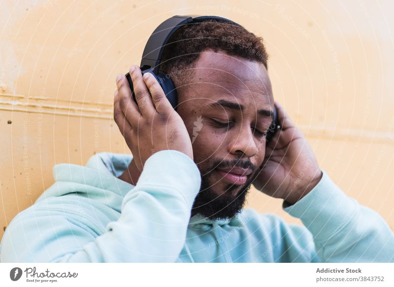 Optimistic black hipster listening to music with headphones man happy enjoy cheerful beard wireless adult african american ethnic male optimist casual device