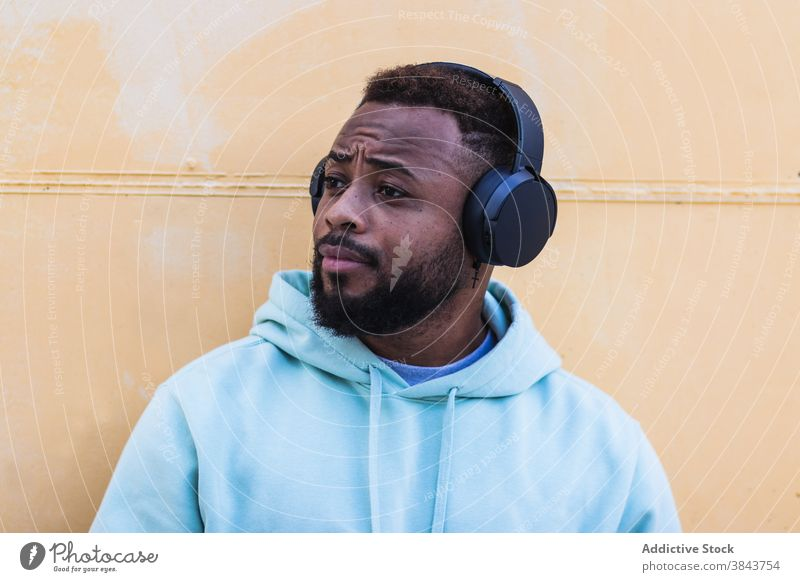 Optimistic black hipster listening to music with headphones man enjoy beard wireless adult african american ethnic male optimist casual device sound gadget
