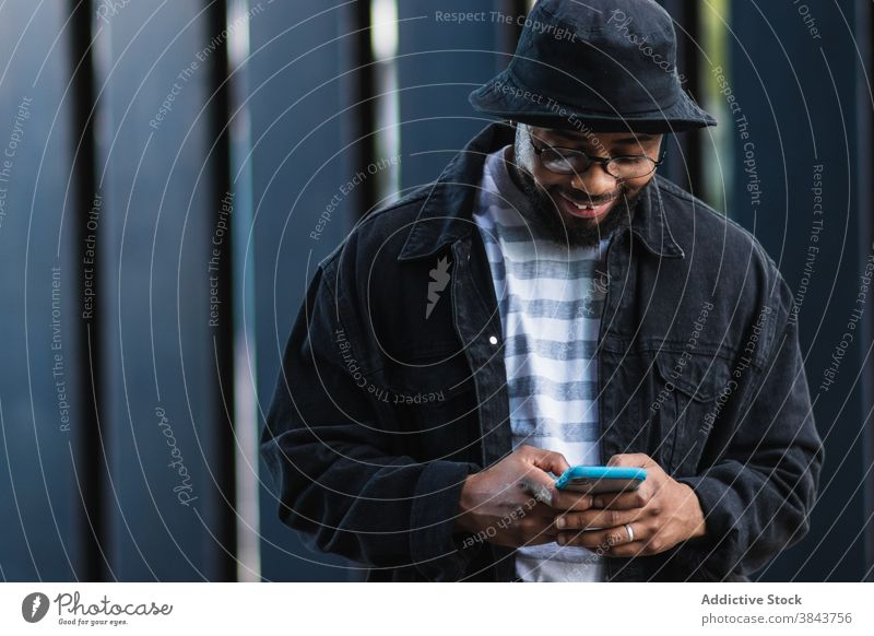 Positive black hipster man using mobile phone smartphone happy cheerful message browsing trendy hat adult african american ethnic male device gadget connection