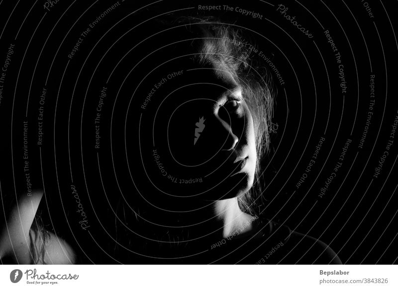 Black and white portrait of an Italian girl on black background dramatic tension beautiful sensual dark sadness illuminated obscure black and white gloomy