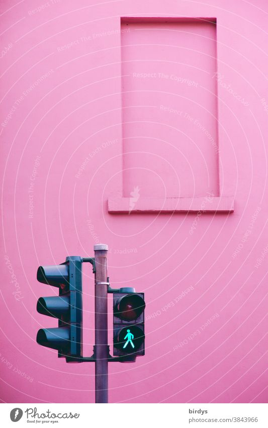 Green pedestrian lights in front of pink wall Traffic light Pedestrian traffic light launch Going Pictogram green light