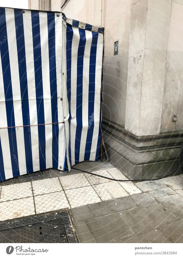 A blue and white striped fruit stand from the side. Tarpaulin, tent, Observations tarpaulin plastic Tent Stripe power cable Pattern Covers (Construction)