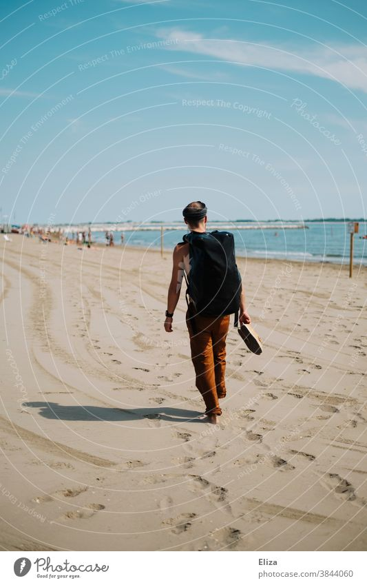 A man with a backpack walks along a beach on vacation and looks at the sea. Beach Man Backpack stroll travel voyager Sandy beach Vacation & Travel Human being
