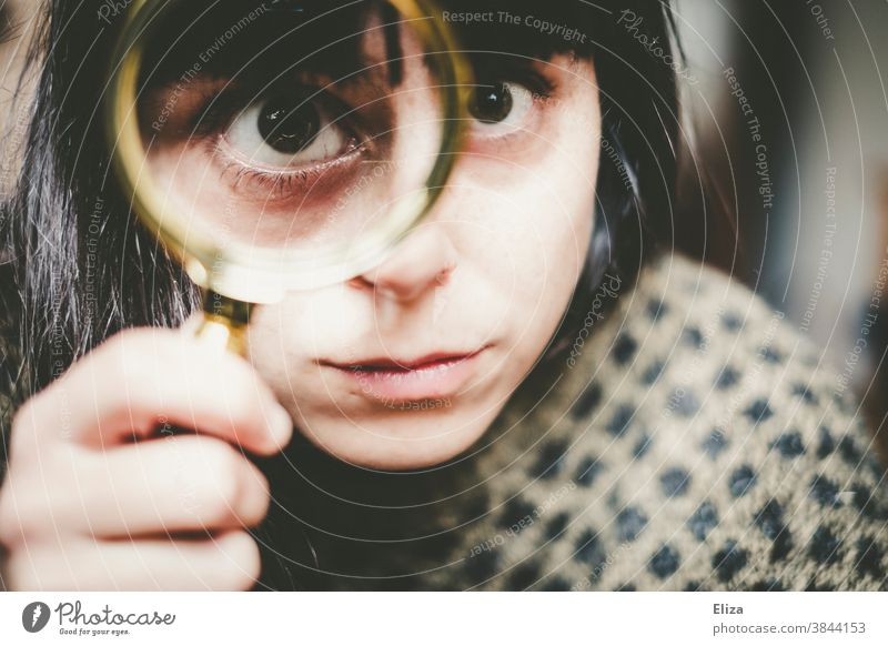 Young woman looks more closely through a magnifying glass. Magnifying glass Enlarged Eyes Investigate test see Squint warped Face search Lens Looking Detective