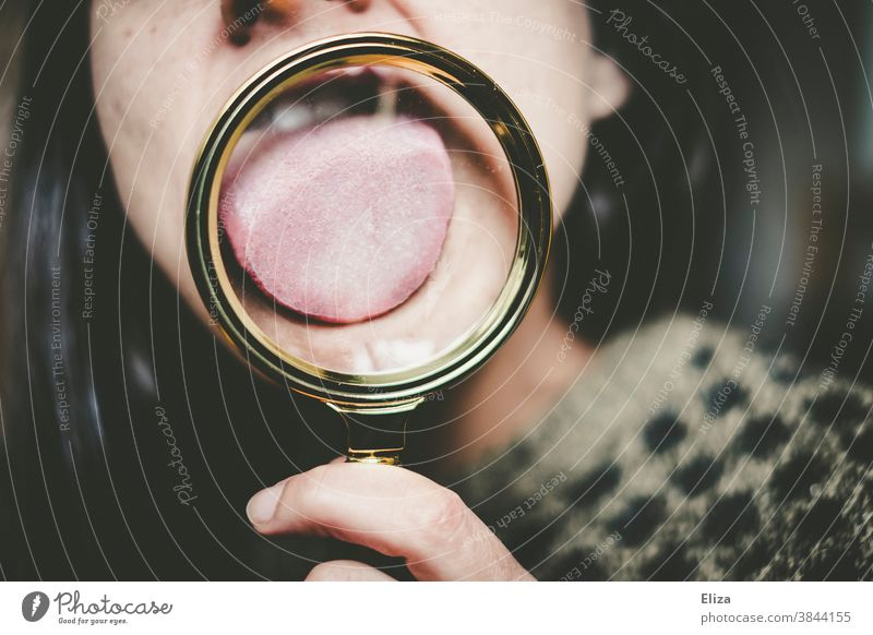 Woman licks a magnifying glass with her tongue. Magnifying glass Tongue taste Sense of taste Enlarged Investigate stick out one's tongue Stick out