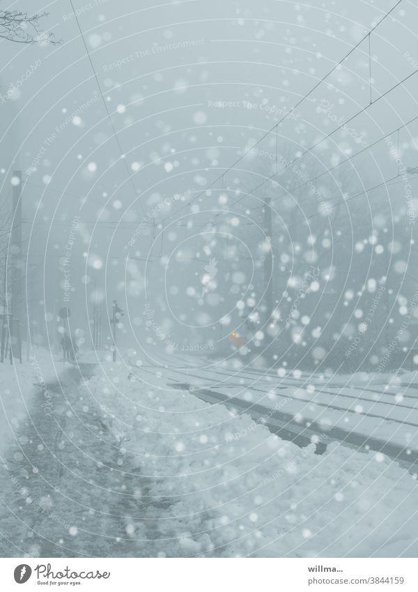 It's snowing in the city, flake swirl. Snow flurries Winter Snowfall snowflakes Street Footpath Railway tracks Snow mud blow snow winter Cold Overhead line