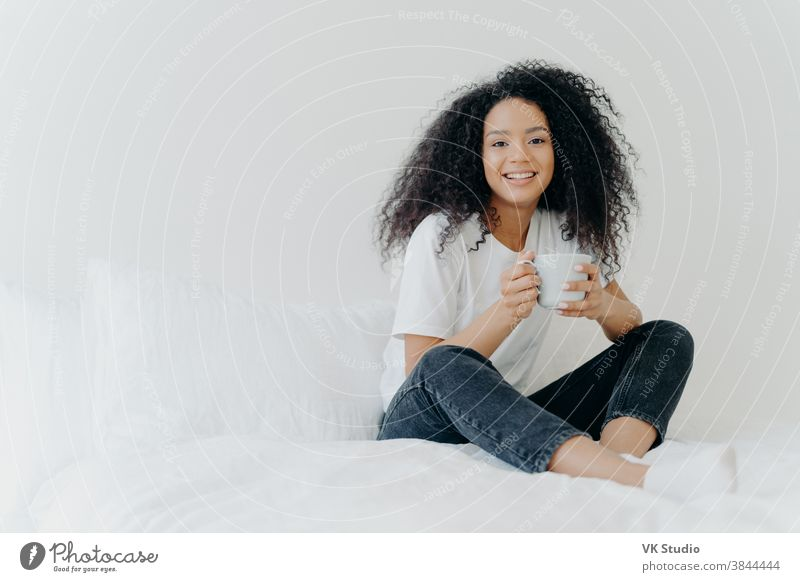 Young pretty African American woman rests in bed at home, drinks hot tea in morning, enjoys domestic atmosphere, tasty drink while relaxes in bedroom. People, leisure, rest and lifestyle concept