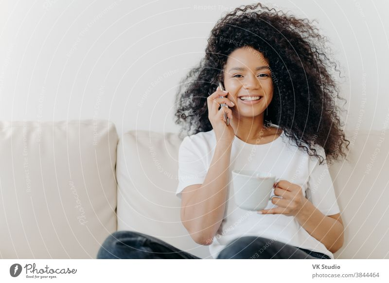 Horizontal shot of good looking woman has distant conversation via mobile phone, solves informal issues while talking, sits on sofa in living room, drinks tea, has broad smile, shows white teeth