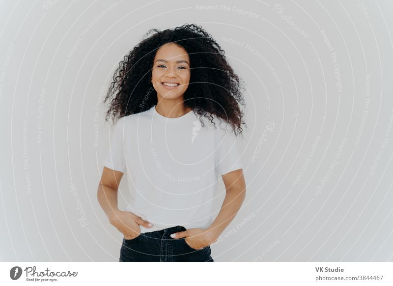 Isolated shot of young African American woman wears white t shirt, expresses good emotions, stands alone indoor, poses for photo, has casual talk with friend, enjoys free time. People and happiness