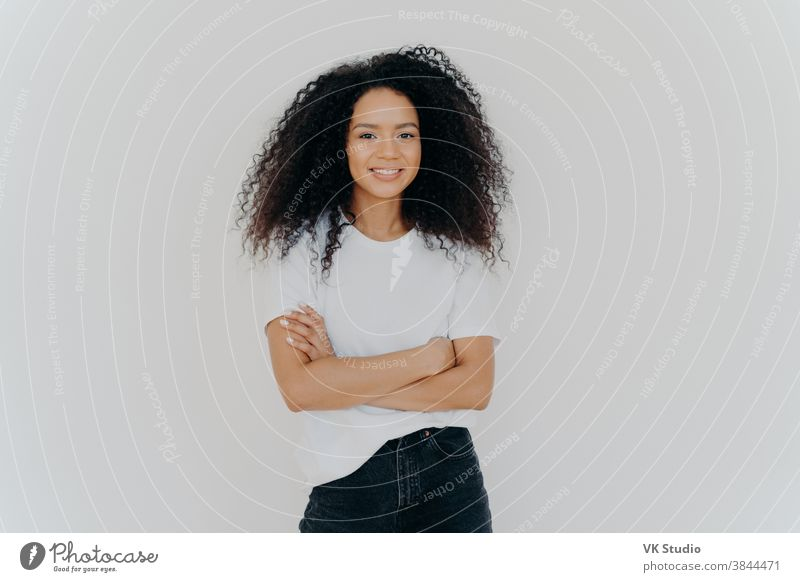 Studio shot of carefree young beautiful woman with Afro hairstyle, keeps arms folded, smiles joyfully, wears casual t shirt and jeans, isolated on white background. People, ethnicity, face expressions