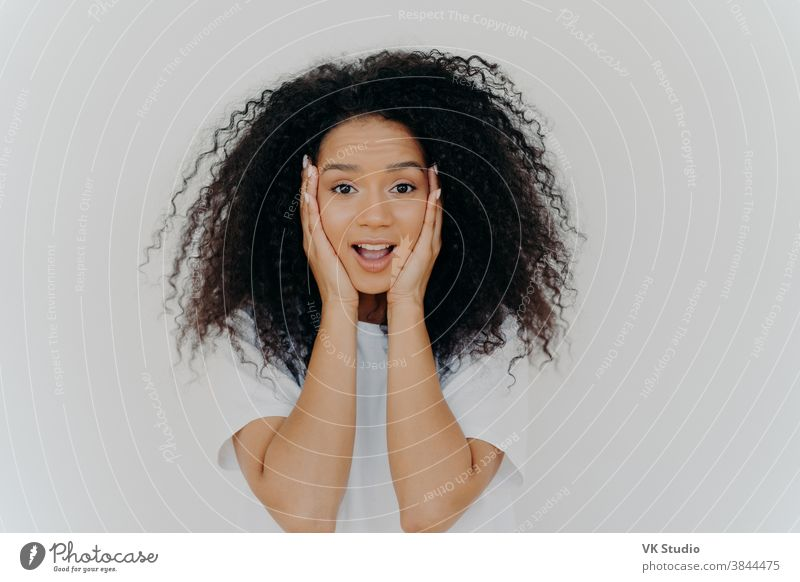 Photo of surprised cheerful woman with Afro haircut, keeps both hands on cheeks, has natural beauty, opens mouth, cannot believe in exciting news, wears t shirt, poses against white background.