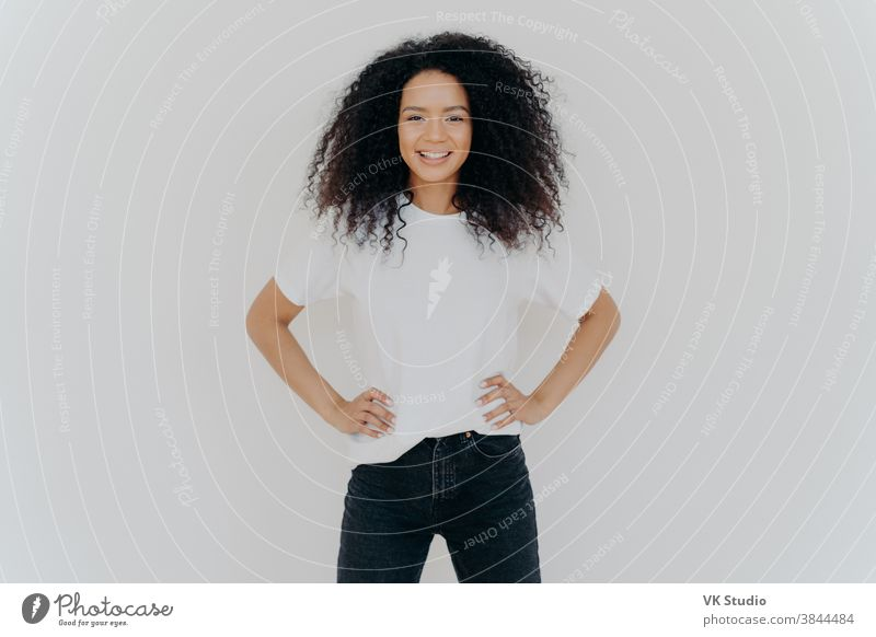 Photo of delighted curly woman keeps both hands on waist, smiles gently, has slim figure, wears white t shirt and black jeans, being in good mood, stands self assured against white background
