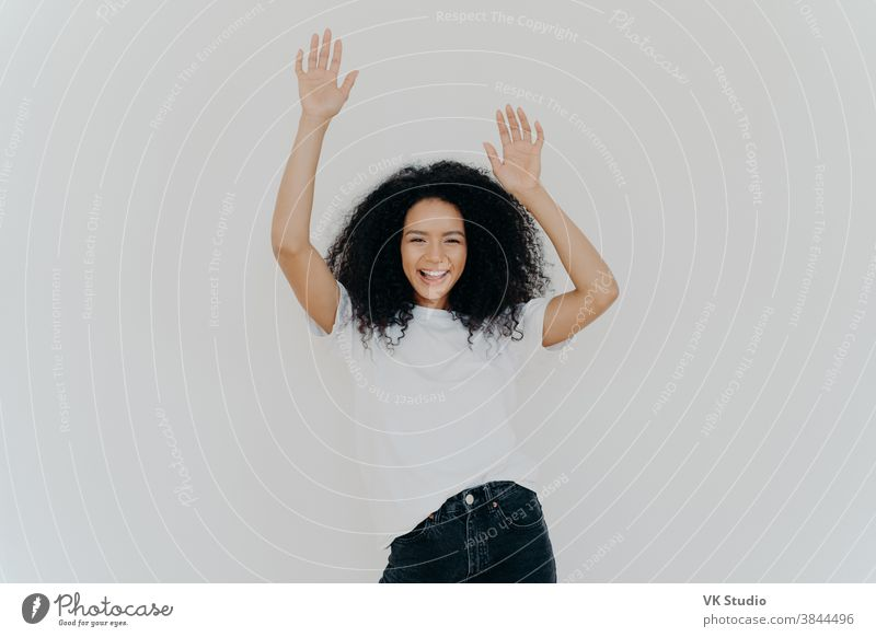Half length shot of energetic carefree curly woman cheers with hands raised, wears white t shirt and jeans, has lucky day, perfect weekend, models against white background. Everybody put your hands up