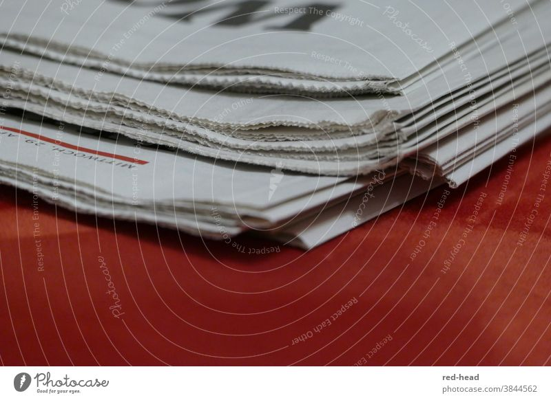 Close-up of a daily newspaper, upper edge, red background, only one corner and fold visible Newspaper Daily newspaper Stack of paper White Red