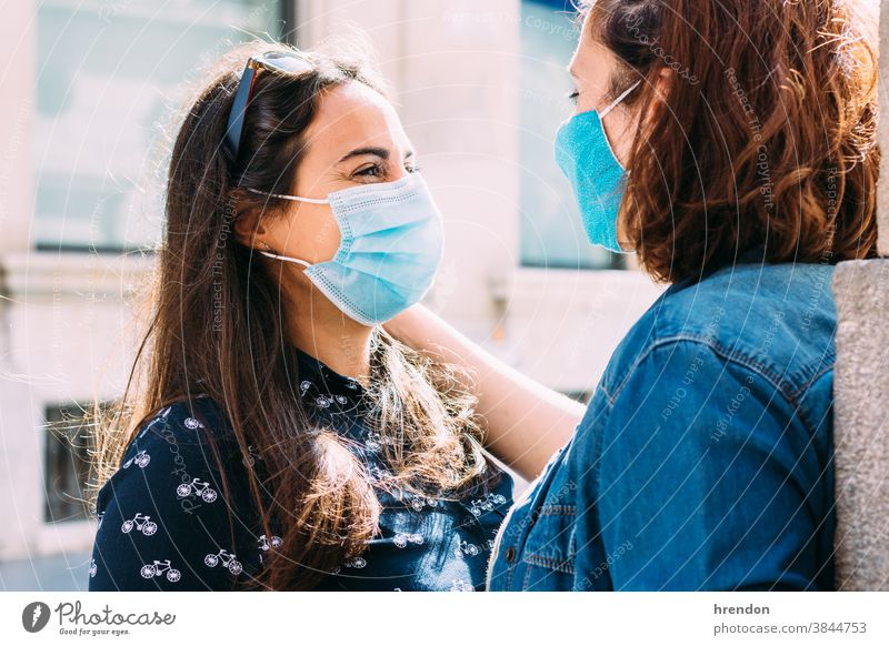 couple of women with a face mask hugging in the street woman lesbian homosexual coronavirus love female covid 19 girlfriend happy lifestyle romance togetherness