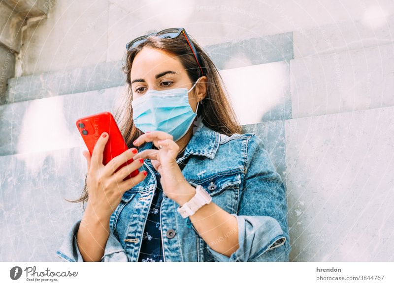 woman with a face mask leaning against the wall using her smartphone female young lifestyle internet communication technology mobile telephone communicate